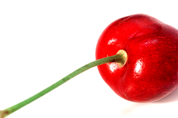 Close up of a cherry on a white surface